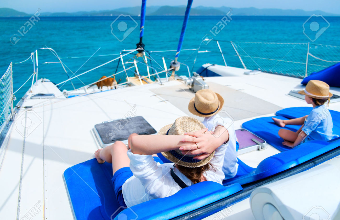 30353819-Back-view-of-mother-and-her-kids-relaxing-having-great-time-sailing-at-luxury-yacht-or-catamaran-boa-Stock-Photo